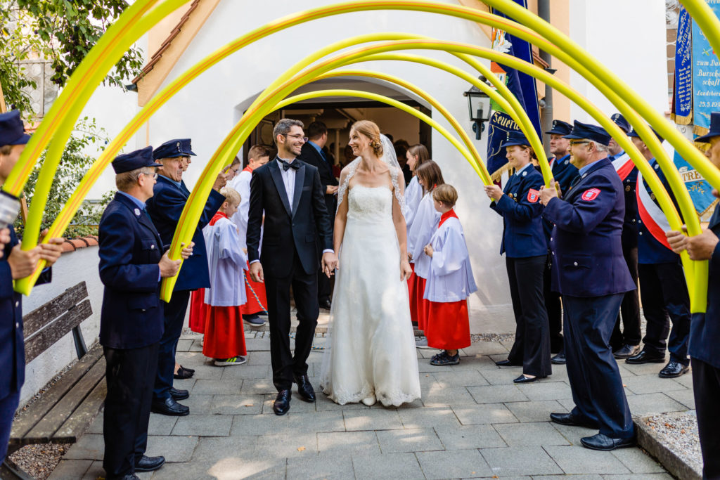 Hochzeitspaar läuft durch einen Spalierbogen - Hochzeitsfotografie Fürstenfeldbruck