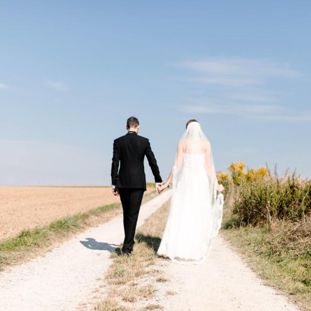 Brautpaar spaziert über einen Feldweg - Hochzeitsfotografie Fürstenfeldbruck