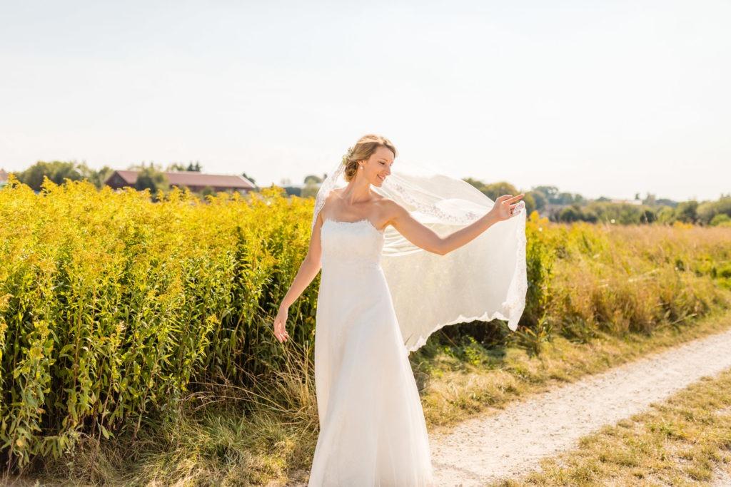 Die Braut hält ihren Schleier im Wind fest - Hochzeitsfotografie Fürstenfeldbruck