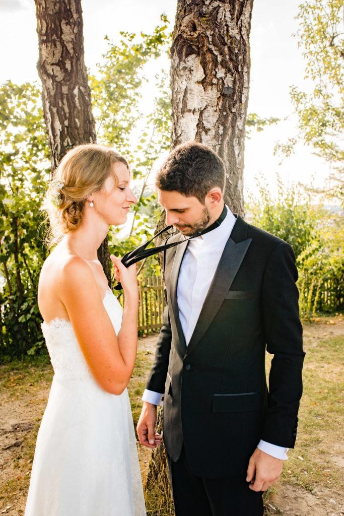 Braut zieht Bräutigam an der Krawatte zu sich - Hochzeitsfotografie Fürstenfeldbruck