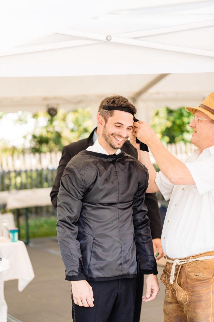 Dem Bräutigam wird die Krawatte an die Stirn gebunden - Hochzeitsfotografie Fürstenfeldbruck