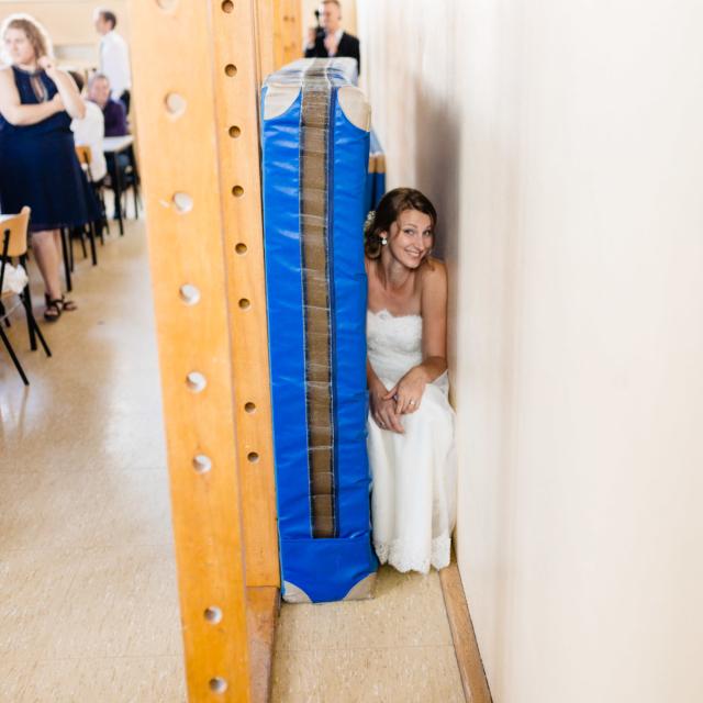 Braut versteckt sich hinter einer Matratze in der Turnhalle - Hochzeitsfotografie Fürstenfeldbruck