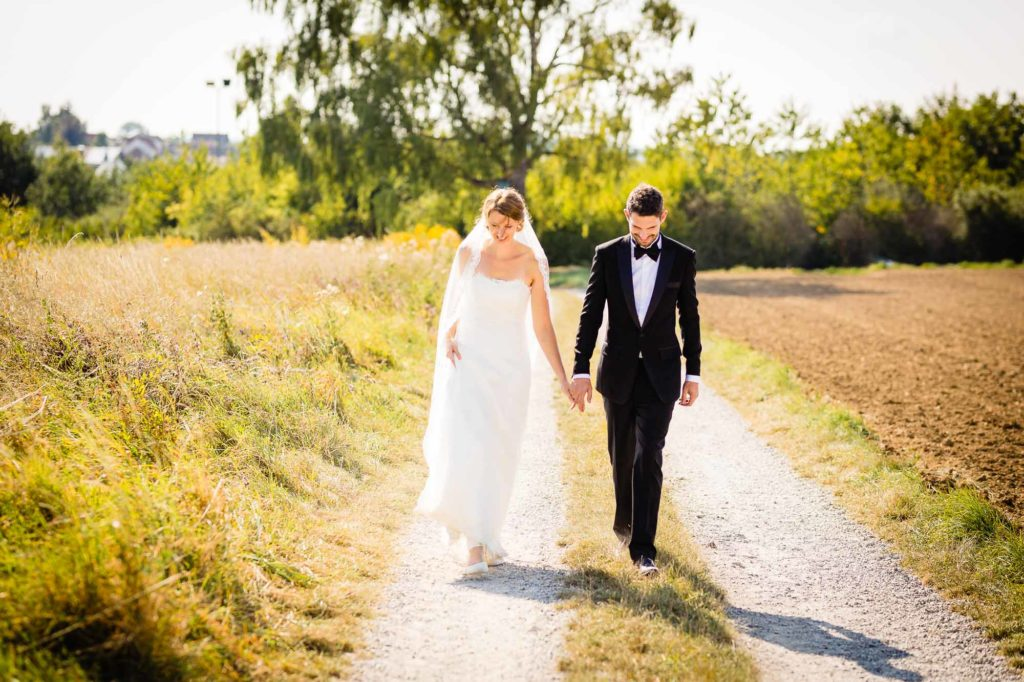 Hochzeitspaar läuft über einen Feldweg