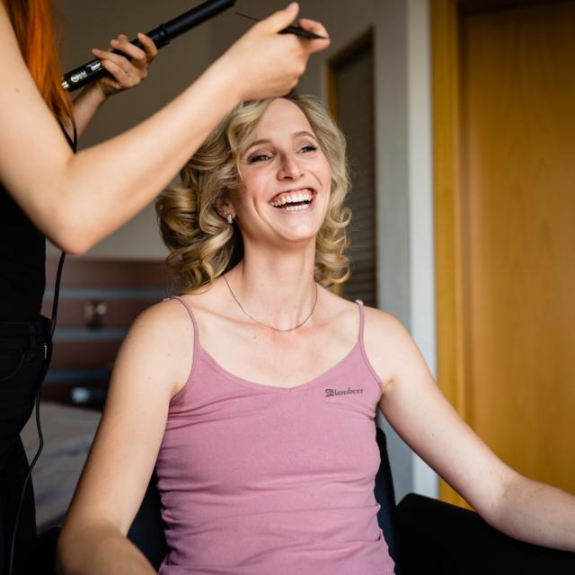 Bild zeigt die lachende Braut mit Stylistin