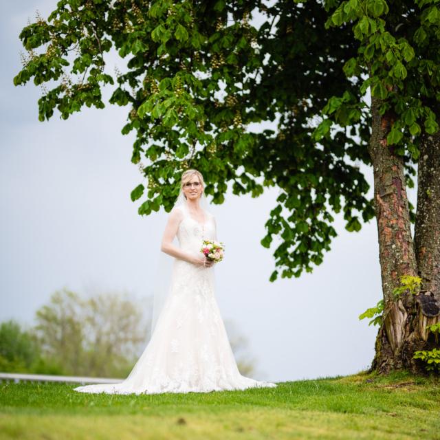 Bild zeigt Braut mit Strauß in der Natur