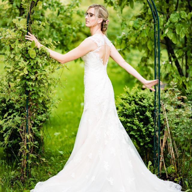 Hochzeitsfotografie von der Braut im Rosenbogen