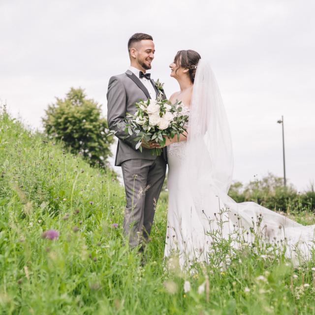 Bild zeigt das lachende Brautpaar im Gras