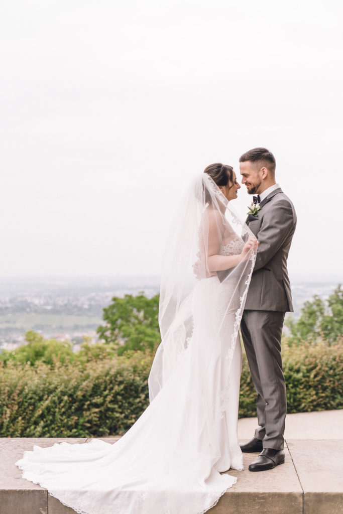 Foto zeigt das Brautpaar auf einer Mauer