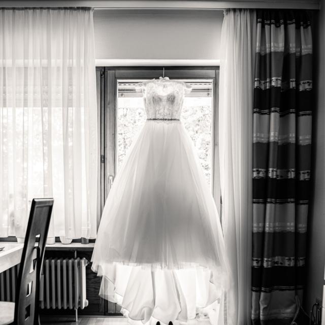 Foto zeigt Hochzeitskleid das am Fenster hängt