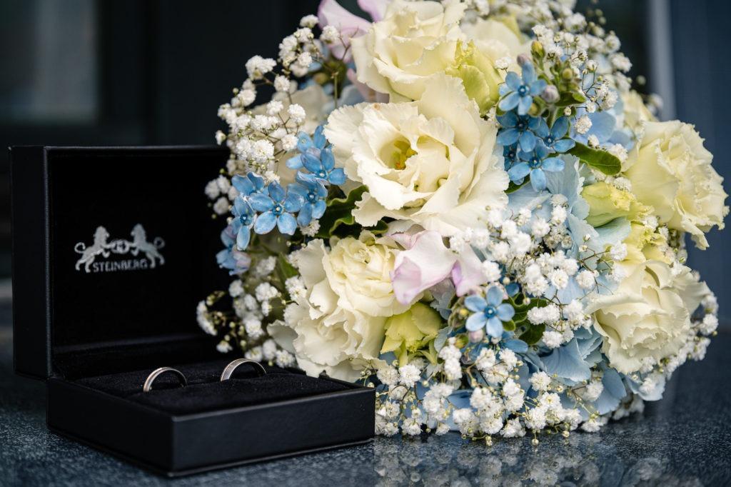 Detailaufnahme der Trauringe mit Brautstrauß