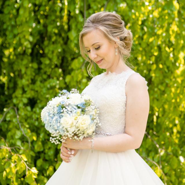 Foto zeigt die Braut vor einem Baum mit Brautstrauß