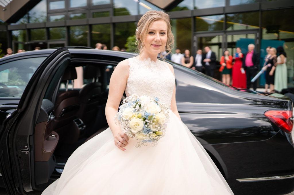 Foto zeigt die Braut die aus dem Auto steigt