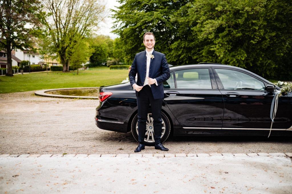 Hochzeitsfoto vom Bräutigam vor dem Auto